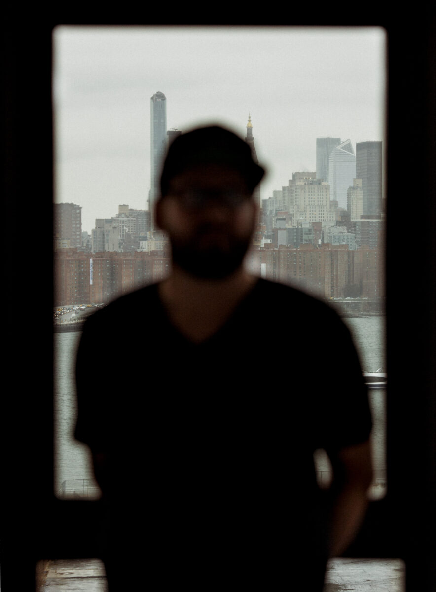 a man standing in front of a window in new york city
