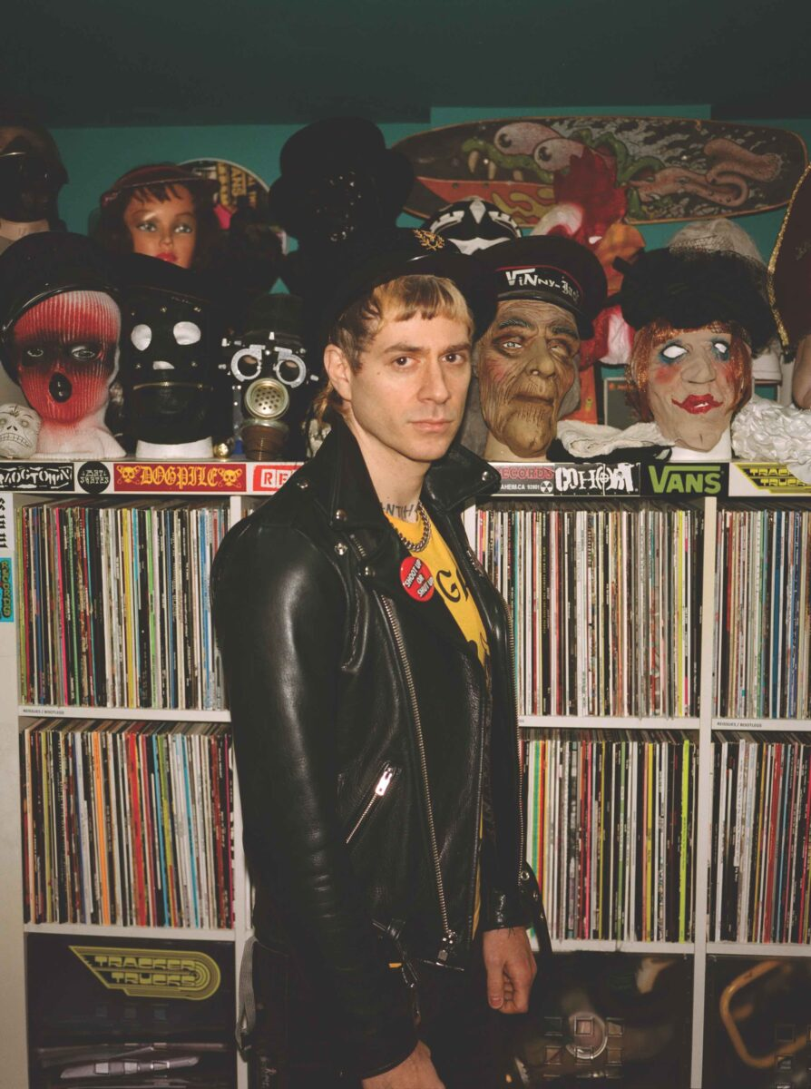 a man standing in front of records and mannequin heads