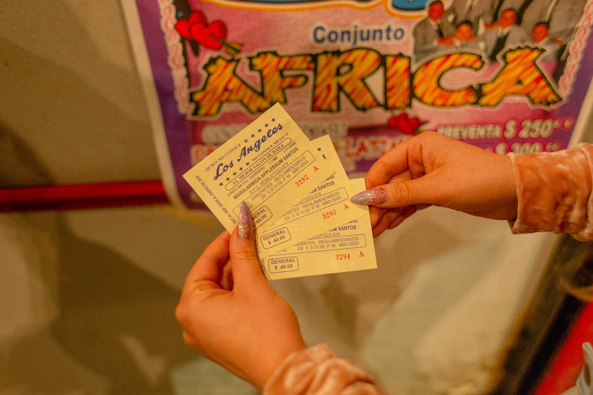 woman's hands with glitter manicure holding tickets to salon los angeles
