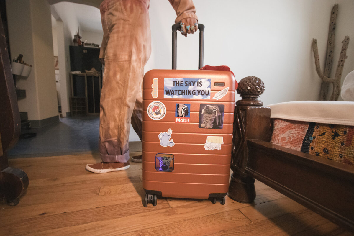 a suitcase covered in stickers