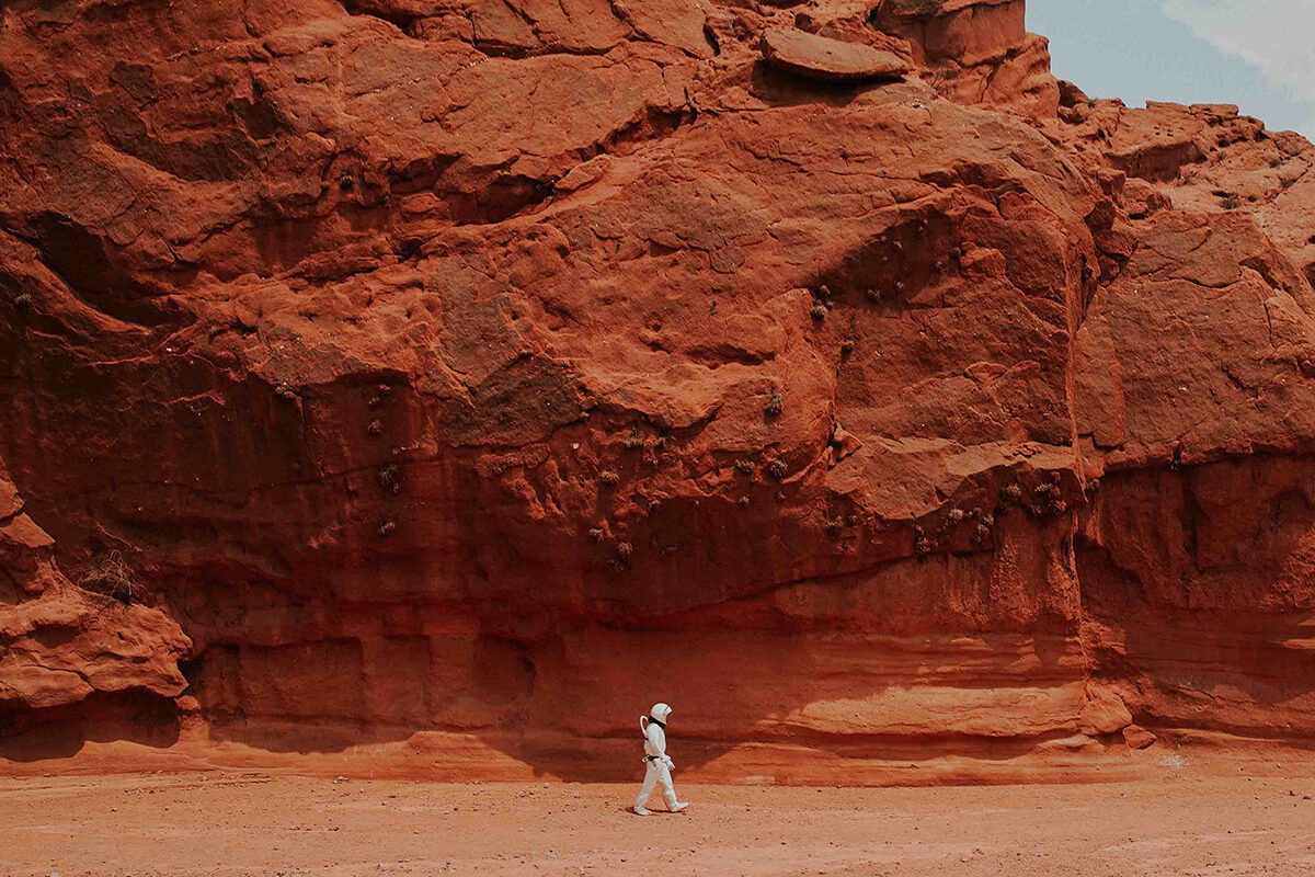 an astronaut walking in rocky landscape