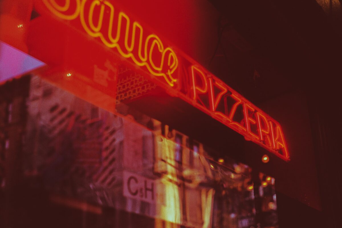 a neon red pizza restaurant sign